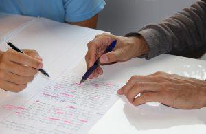 Zdjęcie ilustracyjne: dwie ręce z długopisami nad białą kartką